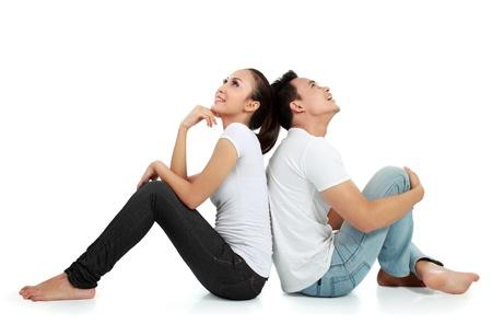 donna pensiero: Ritratto di una bella giovane coppia felice seduta sul pavimento pensare qualcosa di