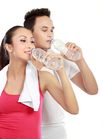 Portrait of sporty healthy young woman and man drinking water isolated on white background Stock Photo - 13409161