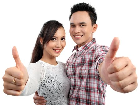 Happy young couple two thumbs up sign photo