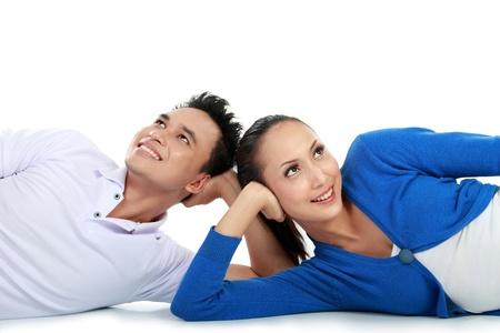 jeune beau couple allongé sur le sol levant les yeux vers l'espace copie Banque d'images