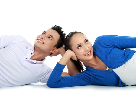 lifestyle looking lovely: young lovely couple lying on the floor looking up to the copy space