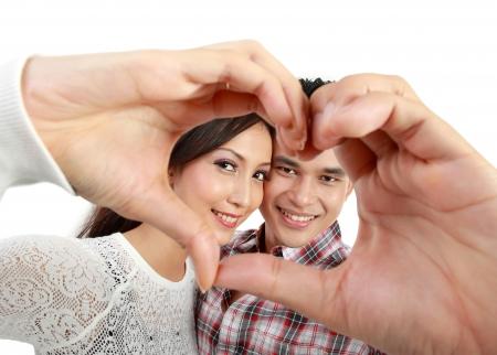 parejas jovenes: Feliz pareja de j�venes enamorados que muestra el coraz�n con los dedos aislados sobre fondo blanco Foto de archivo