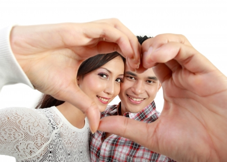 Happy young couple in love showing heart with fingers isolated over white background