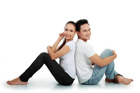 portrait of asian happy couple smiling while sitting on white background photo