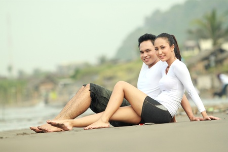 Portrait of a young couple at the beach sitting on the sand photo