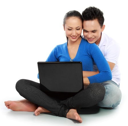 happy Couple with laptop, sitting on white  floor photo