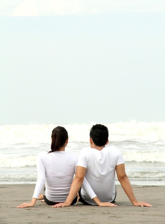 happy asian couple: loving couple relaxing and spending quality time with each other on beach