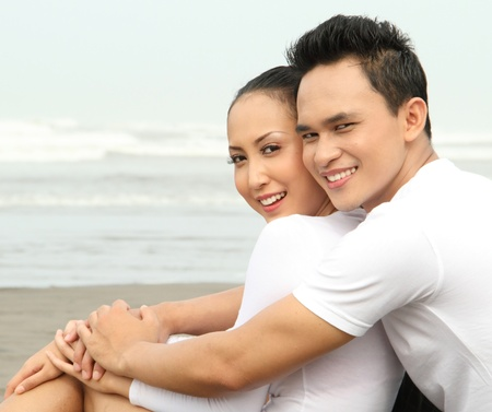 Close up Portrait of a happy young man hugging his girlfriend at the beach photo