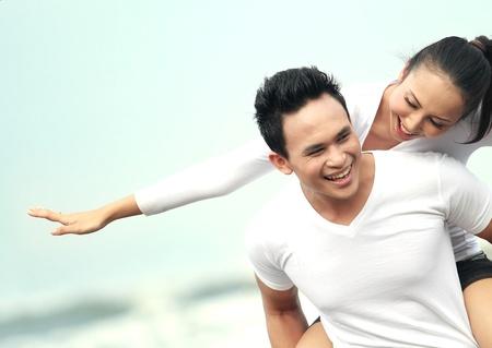 해변에서 여자 피기을주는 젊은 아시아 남자의 초상화를 닫습니다.