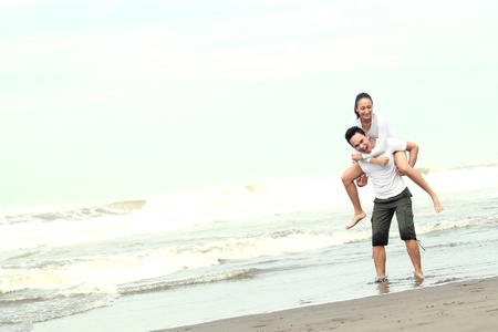 Full body portrait of a young asian man giving piggyback to woman on beach. Stock Photo - 13516291