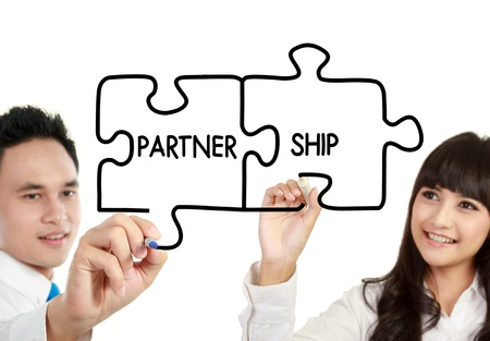 merger: businessman and businesswoman drawing partnership written in puzzle