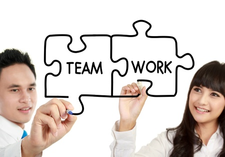 businessman and businesswoman drawing teamwork written in puzzle photo