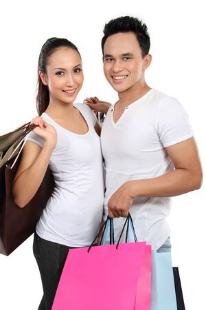 young attractive happy couple carrying shopping bag isolated over white background Stock Photo - 13528208