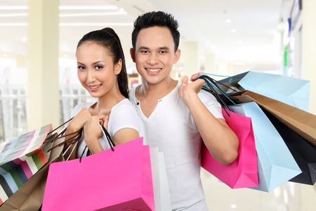 portrait of happy man and woman carrying shopping bag at the mall photo