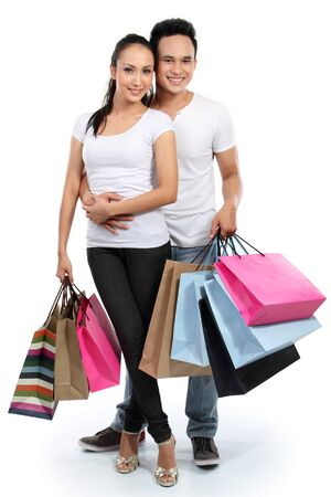 full lenght portrait of happy couple carrying shopping bag on white background Stock Photo - 13528207