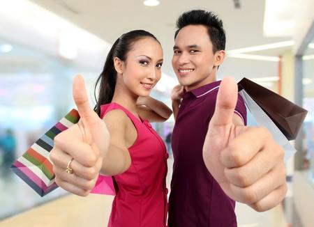 pulgar levantado: atractiva pareja feliz mostrando el pulgar hacia arriba signo mientras que las compras