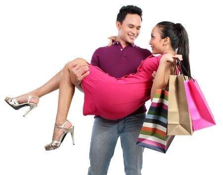 man carrying woman: happy couple after shopping. isolated over white background