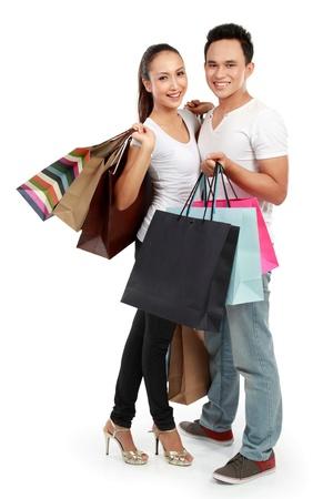 expression corporelle: portrait pleine longueur d'un couple heureux avec un grand nombre de sacs � provisions sur fond blanc