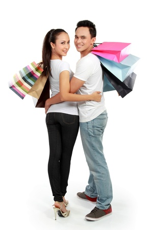 full lenght portrait of happy couple carrying shopping bag on white background Stock Photo - 13528195