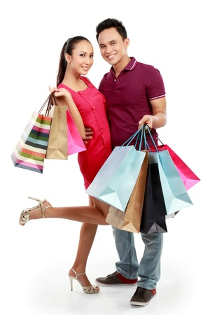 full lenght portrait of happy couple carrying shopping bag on white background photo