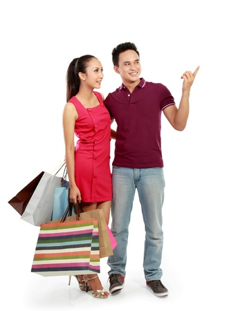 young attractive happy couple carrying shopping bag pointing to something photo