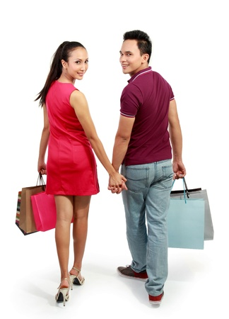 full lenght portrait of happy couple walking with shopping bag on white background photo