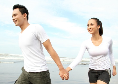 Portrait of a happy young couple having fun on the beach photo