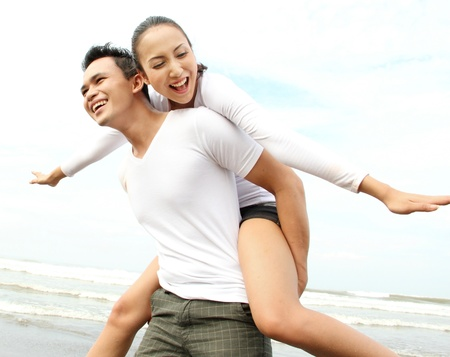 Close up portrait of a young asian man giving piggyback to woman on the beach. photo