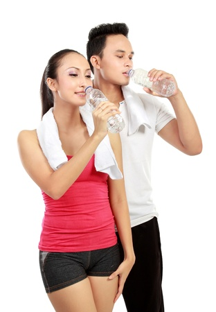 water aerobics: Portrait of sporty healthy young woman and man drinking water isolated on white background Stock Photo