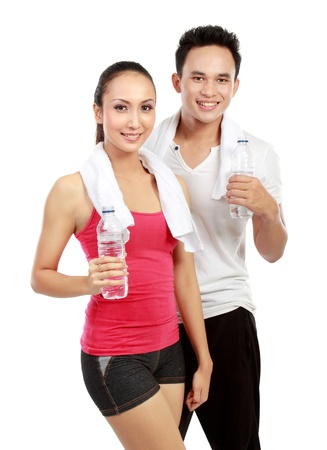 Portrait of sporty healthy young woman and man drinking water isolated on white background photo