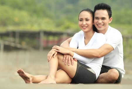 Portrait of a happy young man hugging his girlfriend at the beach Stock Photo - 13602967