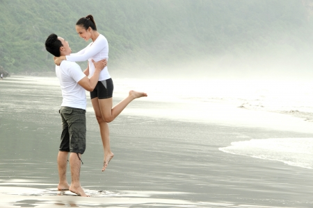 levantar peso: Una feliz pareja atractiva se divierten en la playa