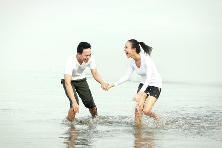 Couple laughing enjoying a summer vacation on the beach photo