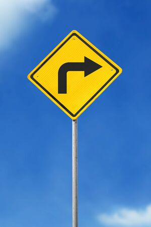 turn sign: turn right yellow road sign on sky background Stock Photo