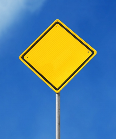Blank yellow road sign on sky background photo