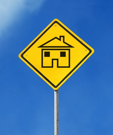 stay alert: yellow house sign on sky background