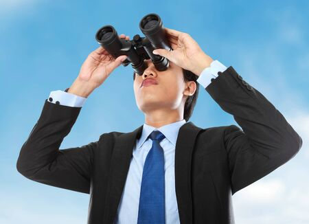 young business man looking through binocular under the blue sky photo
