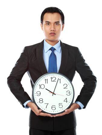 punctual: retrato de hombre de negocios asiático la celebración de un gran reloj aisladas sobre fondo blanco Foto de archivo