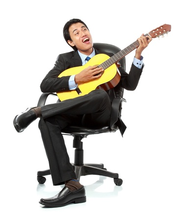 playing music: portrait of asian businessman playing guitar on the chair