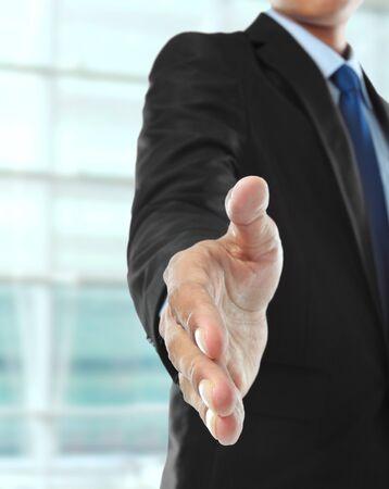 extending: business man extending hand to shake