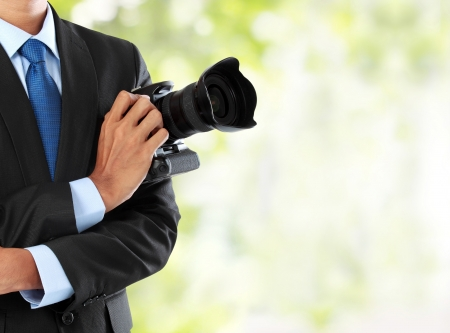 slr: cropped portrait of professional photographer holding dslr camera with copy space Stock Photo