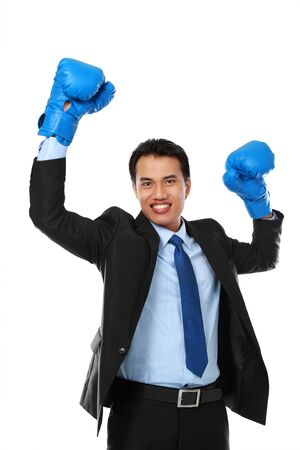 portrait of happy businessman with boxing glove raise his hand photo