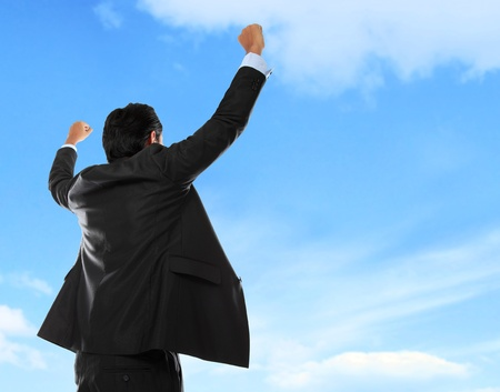 enjoy space: Happy business man with arms raised under the blue sky Stock Photo
