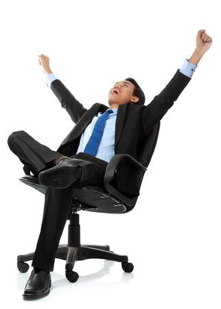 Excited business man with arms raised while sitting - Isolated on white photo