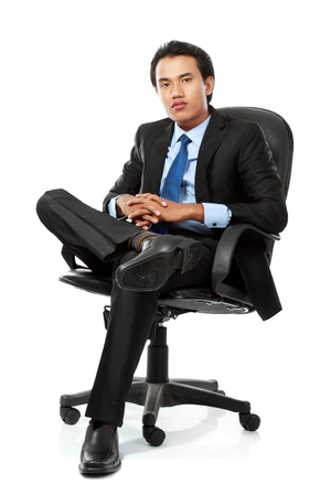 sits on a chair: Relaxed business man sits on office chair isolated over white background Stock Photo