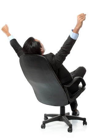 Excited business man with arms raised while sitting on a chair - Isolated on white photo