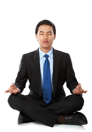 Businessman sitting in lotus position, Isolated against white background photo