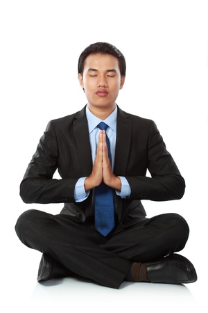 Businessman sitting in yoga position, Isolated against white background photo