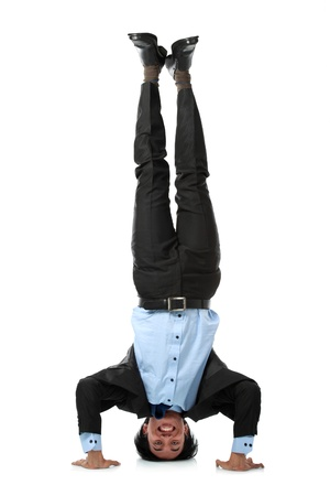 Full length of business man doing headstand isolated over white background photo