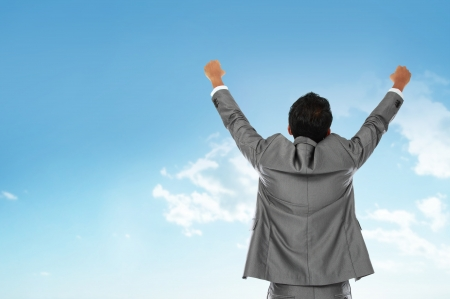 victory: Happy business man with arms raised under the blue sky Stock Photo
